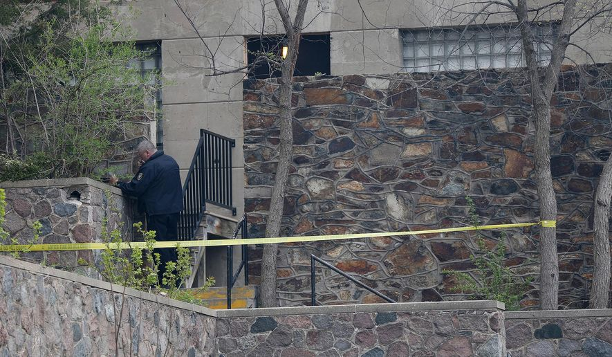 An investigator stands outside an apartment complex after a fatal shooting in Wausau, Wis., Sunday, May 1, 2016. A Wausau police officer fatally shot a man who authorities say was wielding a knife. (Megan McCormick/The Wausau Daily Herald via AP) NO SALES; MANDATORY CREDIT