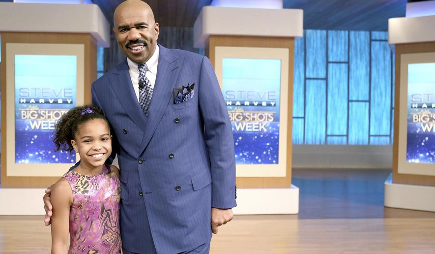 """This April 13, 2016 photo shows Konnor McClain, of Charleston, W. Va., left, posing with host Steve Harvey on the set of the talent show, """"Little Big Shots,"""" in Chicago. McClain is recognized as the best 11-year-old gymnast in the country. She was selected to be part of the pre-Olympic national team and she has dreams of making it to the roster for the 2024 Olympics. (Tegan Kinane/NBC via AP)"""