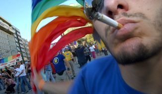 A man smoking a sigarete waves a multi coloured flag during a gay pride parade in central Athens, Greece, on Saturday, June 25, 2005.  More than 500 people attended the first large-scale gay parade in downtown Athens  calling for greater tolerance toward homosexuals. (AP Photo/Petros Giannakouris)