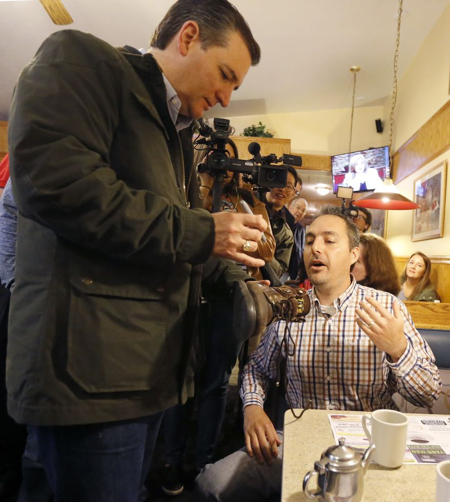 Republican presidential candidate, Sen. Ted Cruz, R-Texas, autographs Randall Perry's boot, during a visits to the Bravo Cafe during a campaign stop, Monday, May 2, 2016, in Osceola, Ind. (AP Photo/Charles Rex Arbogast)