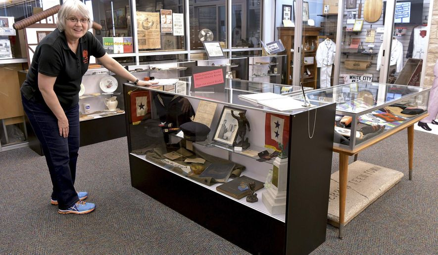 MOVE PHOTO AT 4:00 A.M. CT, MONDAY, MAY 2 - In this March 31, 2016 photo, Lisa Carnaghi, assistant researcher for the Herrin History Room in the Herrin City Library talks about a display case full of World War II memorabilia in Herrin, Ill. Carnaghi says that the history room collection is growing as they constantly are receiving donated items. Herrin has a history that includes coal mines, Italian immigrants, gangsters and even an amusement and entertainment complex. (Richard Sitler/The Southern Illinoisan via AP)  MANDATORY CREDIT