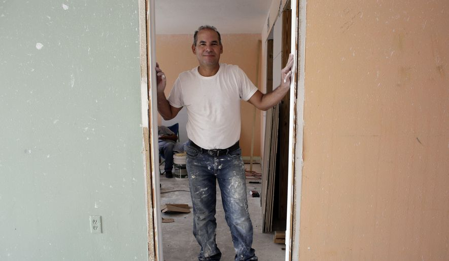 In this Monday, April 25, 2016, photo, Edgar Ospina, 50, poses for a photo where he is remodeling an apartment in Miami Beach, Fla. (AP Photo/Lynne Sladky)