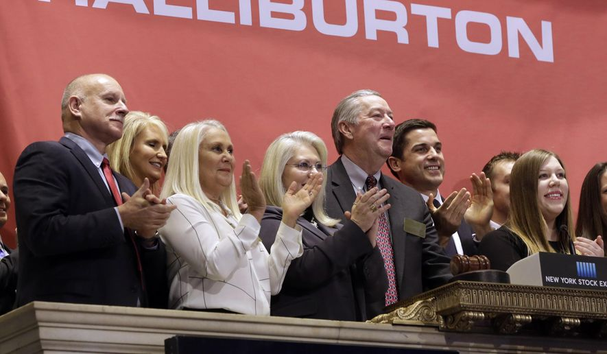 FILE - In a Nov. 18, 2014 file photo, Halliburton Chairman, President and CEO David Lesar, third from right, rings the New York Stock Exchange opening bell. Halliburton and Baker Hughes, two companies crucial to the business of U.S. energy exploration, have abandoned their planned $34 billion merger, the Justice Department said Sunday, May 1, 2016. The department filed suit April 6 to block the merger. (AP Photo/Richard Drew, File)