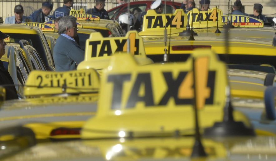A new study finds taxi drivers are likely to overcharge passengers who indicate their fare will be reimbursed by their employer. In this April 26, 2016 file photo taxi drivers line up their vehicles at Heroes' Square during their demonstration against the use of Uber rideshare application in downtown Budapest, Hungary.  (Zoltan Mathe/MTI via AP, file)