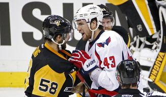 Washington Capitals' Tom Wilson (43) grabs Pittsburgh Penguins' Kris Letang (58) by the sweater during the first period of Game 3 in an NHL hockey Stanley Cup Eastern Conference semifinals in Pittsburgh, Monday, May 2, 2016. (AP Photo/Gene J. Puskar)