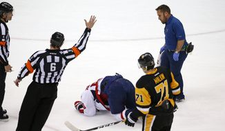 Washington Capitals' Marcus Johansson (90) is helped by a trainer during the first period of Game 3 in an NHL hockey Stanley Cup Eastern Conference semifinals in Pittsburgh, Monday, May 2, 2016. (AP Photo/Gene J. Puskar)