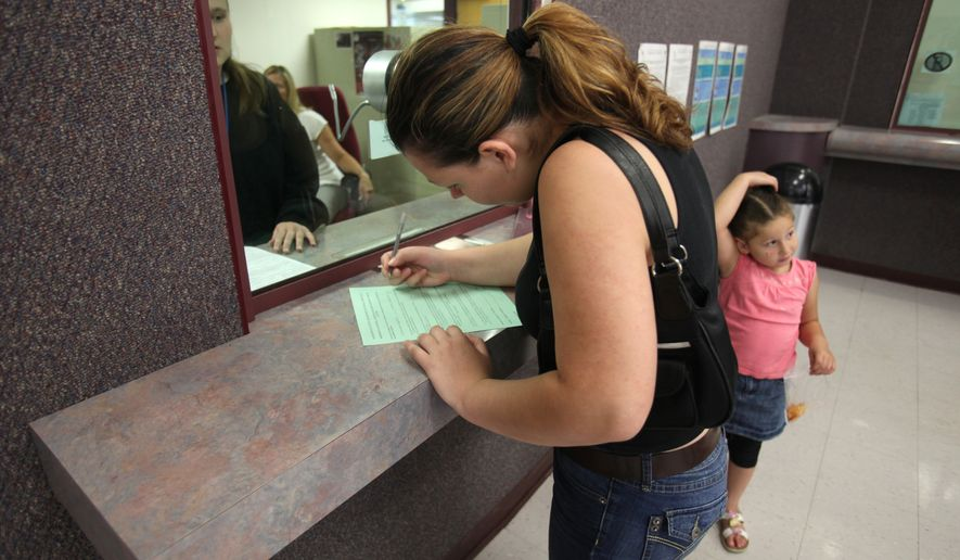 A woman fills out a form at the Sacramento County welfare office in California. (Associated Press/File)