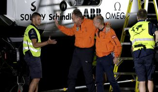 Pilot Andre Borschberg, center, and pilot Bertrand Piccard, right, greet a member of the ground crew after Borschberg exited the cockpit of the Swiss-made Solar Impulse 2 plane, Monday, May 2, 2016, in Goodyear, Ariz. The plane left early Monday from California for a 16-hour trip to Phoenix to resume its journey around the world using only energy from the sun. (AP Photo/Matt York) ** FILE **