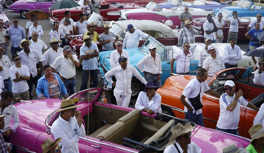 Drivers of vintage American cars receive their final instructions on how to bring in the fashion models that will take part in the upcoming Chanel fashion show, at the parking lot of the Hotel Nacional, in Havana, Cuba, Tuesday, May 3, 2016. (AP Photo/Ramon Espinosa)