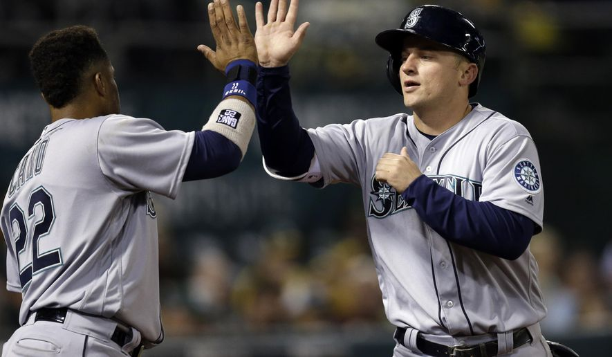 Seattle Mariners' Kyle Seager, right, celebrates with Robinson Cano (22) after scoring against the Oakland Athletics in the sixth inning of a baseball game Monday, May 2, 2016, in Oakland, Calif. (AP Photo/Ben Margot)