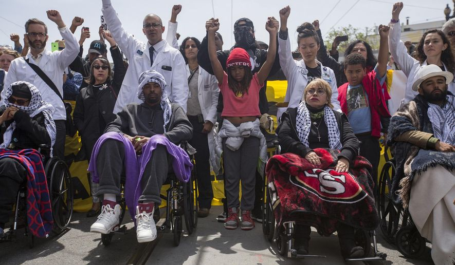 Hunger strikers from left, Ilyich Sato, Sellassie Blackwell, Maria Cristina Gutierrez and Edwin Lindo are wheeled during a protest march to City Hall from the Mission Police Station in San Francisco on Tuesday, May 3, 2016. Five San Francisco residents have been on a hunger strike for thirteen days calling for the resignation of police chief Greg Suhr to protest two recent shooting deaths of minorities by police and racist and homophobic texting scandals involving officers. (Jessica Christian/The San Francisco Examiner via AP) MANDATORY CREDIT