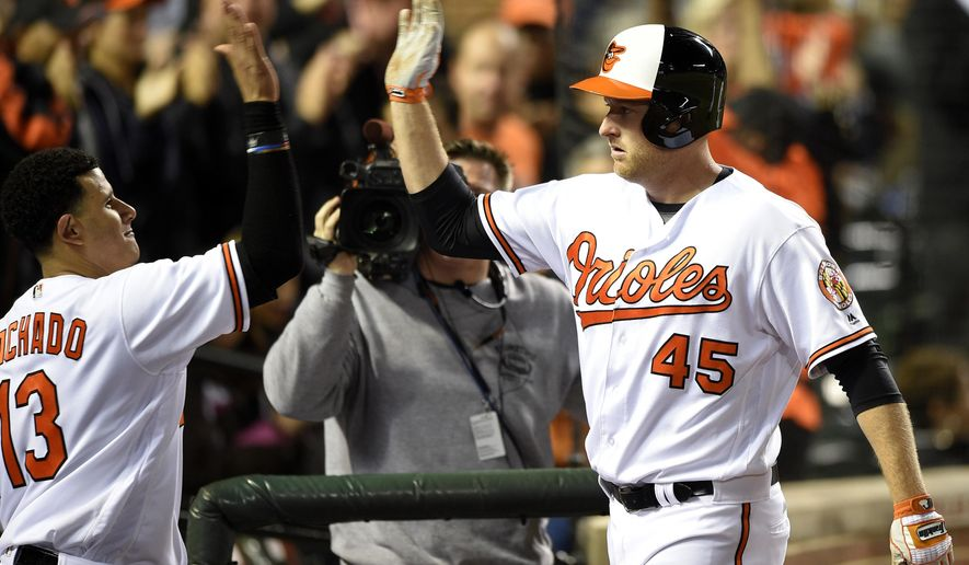 Baltimore Orioles' Mark Trumbo (45) celebrates his two-run home run with teammate Manny Machado (13) during the fifth inning of a baseball game against the New York Yankees, Tuesday, May 3, 2016, in Baltimore. (AP Photo/Nick Wass)