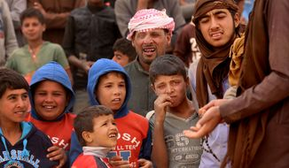 Syrian refugees await approval to enter Jordan at the Hadalat reception area on the Syrian-Jordanian border, about 320 kilometers (200 miles) northeast of the capital of Amman, Wednesday, May 4, 2016. The commander of Jordan's Border Guard Forces says the number of Syrian refugees amassed in remote desert areas on the Jordanian border and waiting to enter has risen to a new high of 59,000. (AP Photo/Raad Adayleh)