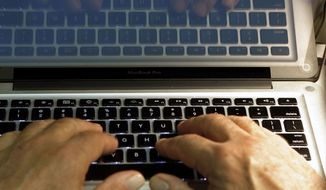 Hands type on a computer keyboard in Los Angeles. (AP Photo/Damian Dovarganes, File)