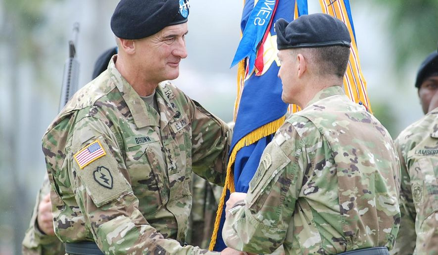 Incoming U.S. Army Pacific commander Gen. Robert Brown, left, receives the command flag from Army Vice Chief of Staff Gen. Daniel Allyn during a change of command ceremony at Fort Shafter, Hawaii, Wednesday, May 4, 2016. Brown is succeeding Gen. Vincent Brooks as the commander of U.S. Army Pacific. (AP Photo/Audrey McAvoy)