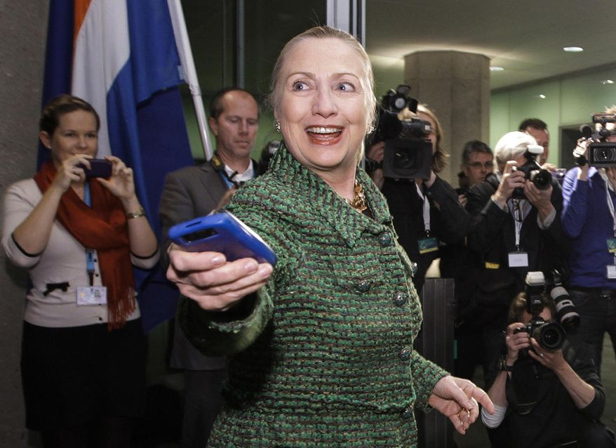 In this Dec. 8, 2011, file-pool photo, then-Secretary of State Hillary Rodham Clinton hands off her mobile phone after arriving for a meeting in The Hague, Netherlands. (AP Photo/J. Scott Applewhite, Pool, File)