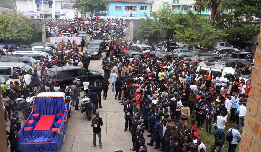 """People gather outside a church during the funeral of Congolese musician Papa Wemba, in Kinshasa, Congo, Wednesday, May 4, 2016. Papa Wemba, known around the world as """"the king of Congolese rumba,""""  died following a collapse on stage during a concert on April 24, 2016. (AP Photo/John Bompengo)"""