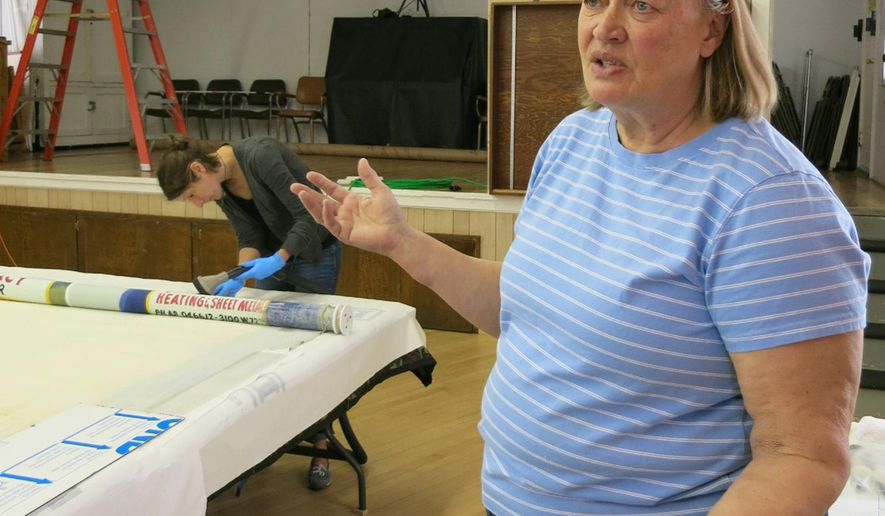 Christine Hadsel, a Vermont-based conservationist who travels the United States to study and preserve early American theatre artifacts, talks about the effort to restore the blocks of advertising on the theatre curtain in a Grange Hall in Westminster, Colo., on Wednesday, May 4, 2016. Hadsel and a colleague from Curtains Without Borders will be touring the state to check theatre artifacts in Silver Plume, Longmont and Aurora this week. (AP Photo/Donna Bryson)