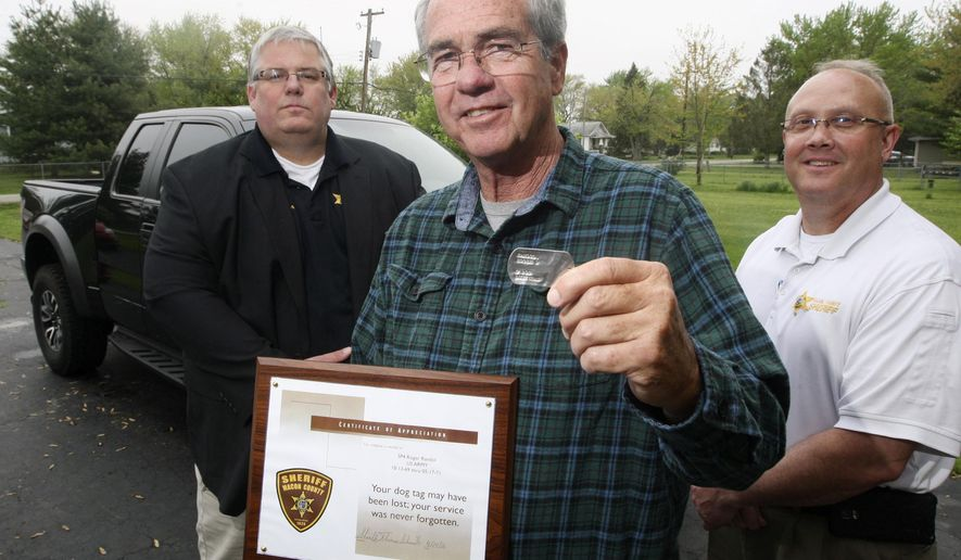 In this April 27, 2016 photo, Vietnam veteran Roger Randol, center, holds a dog tag in Decatur, Ill., that was returned to him after being lost for 45 years. Random lost the dog tag in 1971 shortly after returning from his overseas hitch in the Army during the Vietnam War. A farmer found it and handed it over to authorities, who were able to track Randol down and return the stainless steel tag. Looking on are Macon County Sheriff Tom Schneider, left, and Macon County Sheriff administrative Lt. Jon Butts. (Jim Bowling/Herald & Review via AP) MANDATORY CREDIT