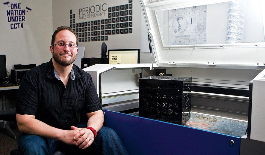 ADVANCE FOR WEEKEND EDITIONS, MAY 7-8 - In this photo taken April 14, 2016, University of Wyoming graphic design assistant professor Brandon Gellis sits in front of a Full Spectrum 36x24 Lazer in the Visual Arts Lab in Laramie, Wyo Students are using the laser to create cutouts and engravings from various materials for their art projects. (Jeremy Martin/Laramie Daily Boomerang via AP) MANDATORY CREDIT