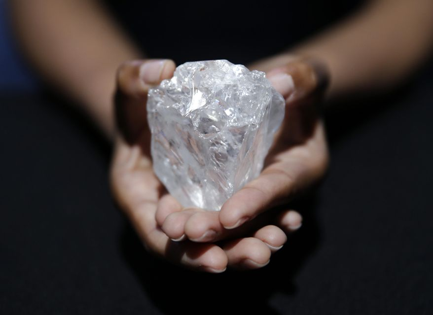 A model displays a large diamond at Sotheby's in New York, Wednesday, May 4, 2016. The auction house plans to offer the Lesedi la Rona diamond in London on June 29. (AP Photo/Seth Wenig)