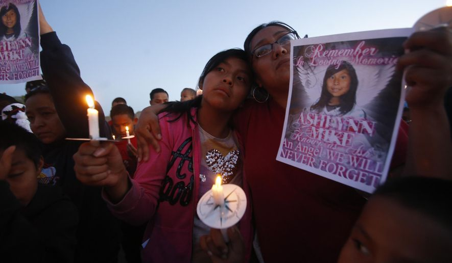 This Tuesday, May 4, 2016, photo Klandre Willie, left, and her mother, Jaycelyn Blackie, participate in a candlelight vigil, for Ashlynne Mike at the San Juan Chapter House in Lower Fruitland, N.M.  The FBI said Mike, was abducted after school on Monday and her body was found the next day.  Tom Begaye was arrested in connection with Mike's disappearance and death. (Jon Austria/The Daily Times via AP)