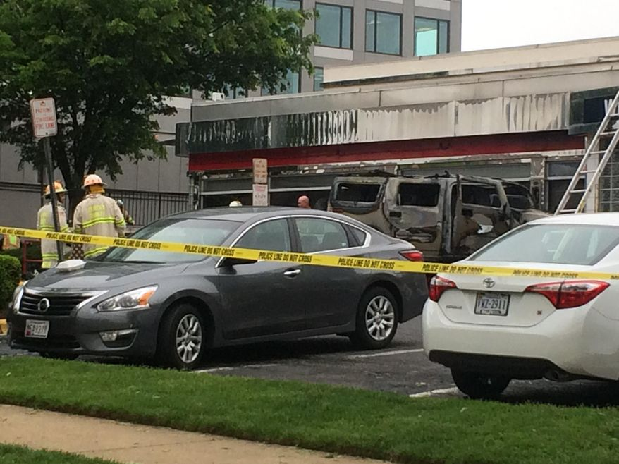 Fairfax County, Va. Fire and Rescue  stand near a restaurant in Tysons Corner, Va., Wednesday, May 4, 2016, after a sport-utility vehicle crashed in front the restaurant and caught fire. Four people have been taken to the hospital, Fairfax County fire and rescue chief Richard Bowers said that none of the injuries appears to be life-threatening. (AP Photo/Matthew Barakat)