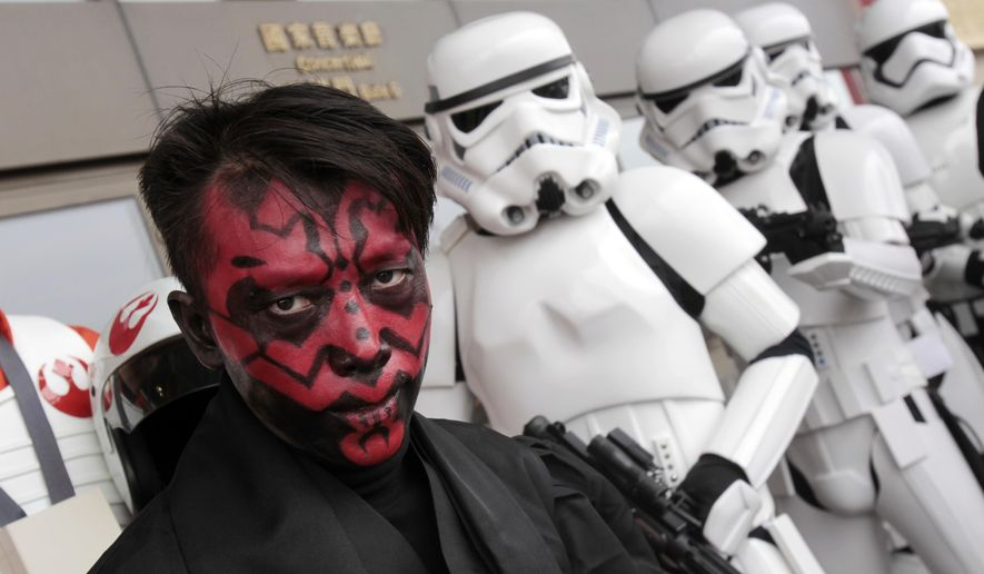 "Fans dressed as movie Star Wars characters pose as they cerebrate the Star Wars Day in Taipei, Taiwan, Wednesday, May 4, 2016. May 4 is known as Star Wars Day to fans worldwide since the date is similar to the franchise's slogan, ""May the Force Be With You."" (AP Photo/Chiang Ying-ying)"