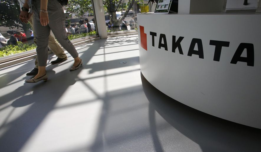 Visitors walk by child seats, manufactured and displayed by Takata Corp. at an automaker's showroom in Tokyo Wednesday, May 4, 2016. U.S. auto safety regulators are in talks with Takata Corp. to add tens of millions of air bag inflators to what already is the biggest auto recall in American history, three people briefed on the matter said Tuesday. (AP Photo/Shizuo Kambayashi)