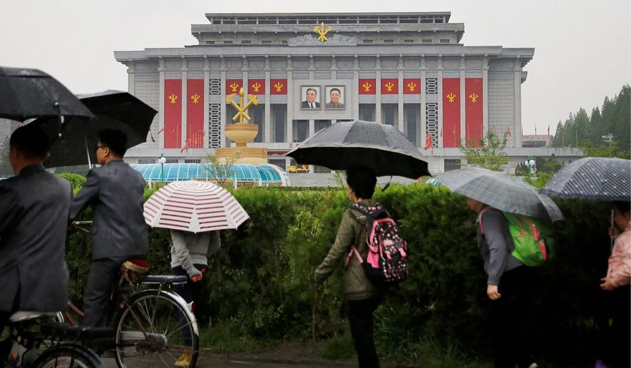 North Koreans carry umbrellas as they walk past the House of Culture, decorated in the colors and flags of their ruling party, the Workers' Party, in Pyongyang. Members of North Korea's ruling party have gathered in Pyongyang ahead of their biggest political conference in decades. (Associated Press photographs)