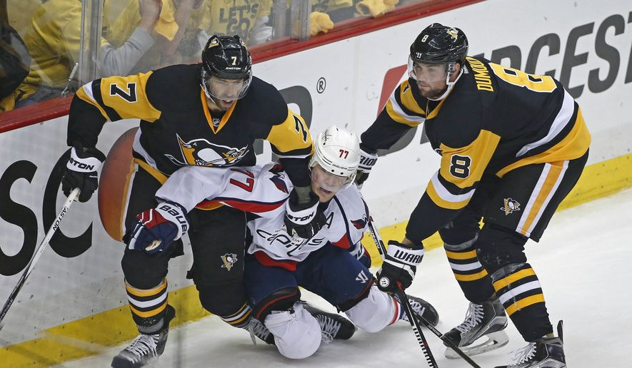 Washington Capitals T.J. Oshie (77) is sandwiched between Pittsburgh Penguins Matt Cullen (7) and Brian Dumoulin (8) during the first period of Game 4 in an NHL hockey Stanley Cup Eastern Conference semifinals in Pittsburgh, Wednesday, May 4, 2016. (AP Photo/Gene J. Puskar)