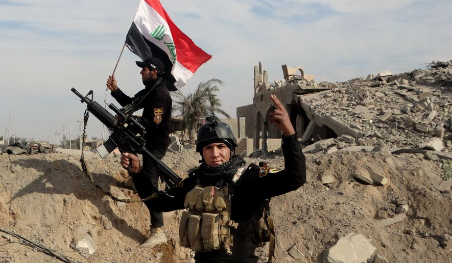 Iraqi counterterrorism soldiers raise an Iraqi flag on the ruins of a building near the provincial council headquarters in Ramadi on Dec. 27, 2015, during the offensive that freed the Iraqi city from nearly a year of rule by the Islamic State group. (Associated Press) **FILE**
