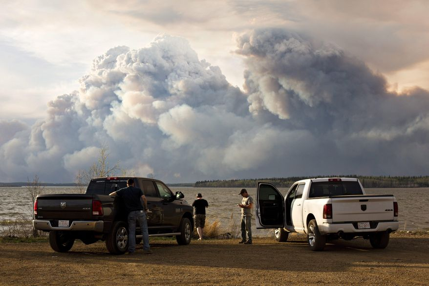 Evacuees watch the wildfire near Fort McMurray, Alberta, on Wednesday, May 4, 2016. Alberta declared a state of emergency Wednesday as crews frantically held back wind-whipped wildfires.  No injuries or fatalities have been reported. (Jason Franson/The Canadian Press via AP) MANDATORY CREDIT