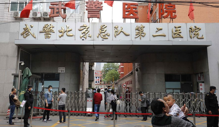 """In this Wednesday, May 4, 2016 photo, a man carries a child past the gate with the words """"Second Hospital of Beijing Armed Police Corps"""" in Beijing, China. Chinese media reports said the Second Hospital of the Beijing Armed Police Corps had outsourced the administration of its oncology department to a private company which allegedly sought profits by offering ineffective, unnecessary or unapproved medical treatments.(Chinatopix Via AP) CHINA OUT"""