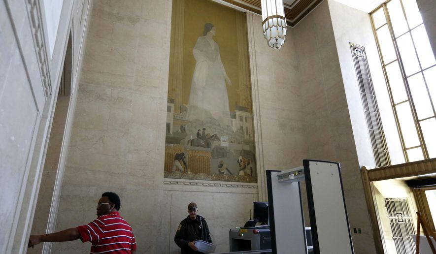 A man walks in front of a mural on the wall of the Birmingham, Ala., courthouse, Thursday, May 5, 2016. Jefferson County Commission members said Thursday that they'll work together to address concerns surrounding two murals in the county courthouse building that members of a local NAACP branch have said are offensive and should be removed.  (AP Photo/Brynn Anderson)