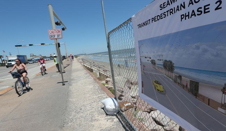 Cyclists ride past a banner hanging near 45th Street on Wednesday, May 4 2016, that shows an artists rendering of improvements planned along the seawall in Galveston, Texas. The city in the coming months will install new bus stops on the seawall, using funds generated by paid parking along the seawall. (Jennifer Reynolds/The Galveston County Daily News via AP) MANDATORY CREDIT, NO SALES, TV OUT