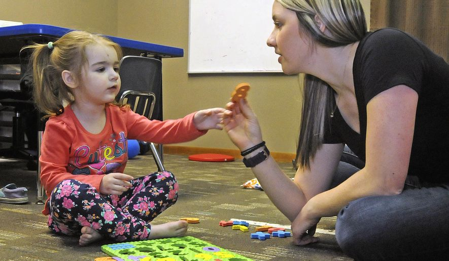 ADVANCE FOR USE SUNDAY, MAY 8 AND THEREAFTER - In this April 26, 2016 photo, MiKynna Cummings, left, works on numbers with occupational therapist Sara Joersz at the Red Door Pediatric Therapy center in Bismarck, N.D. MiKynna, who was diagnosed with autism when she was 15 months old, comes to Red Door Pediatric Therapy in Bismarck three times a week for speech and occupational therapy sessions. (Tom Stromme/The Bismarck Tribune via AP) MANDATORY CREDIT