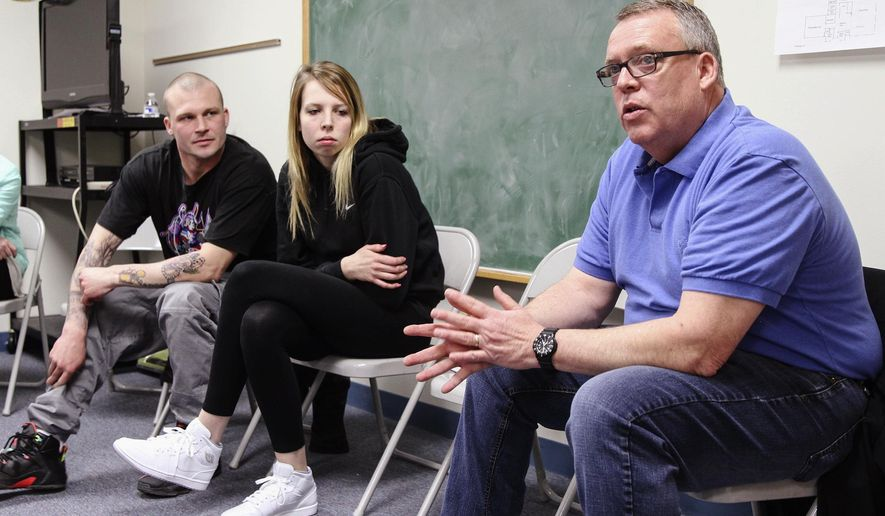 ADVANCE FOR USE SUNDAY, MAY 8 AND THEREAFTER - In this April 5, 2016 photo, Tom Moore, right, of New Lenox, Ill., leads a discussion during an opiate recovery support group at Peace Lutheran Church in New Lenox. Moore's daughter, Ali Moore, and her boyfriend, Dale Burk, both recovering heroin addicts, listen at left. (Lauren Leone-Cross/The Herald-News via AP) CHICAGO TRIBUNE OUT, MANDATORY CREDIT