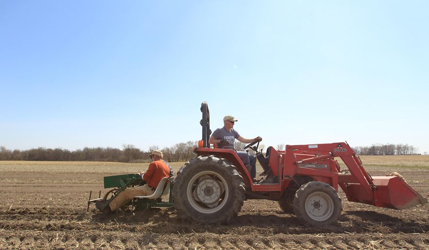 In this photo taken April 13, 2016, Jason Grimm drives a tractor as John Boller and Scott Koepke plant potatoes on a plot of land on Melrose Avenue west of Iowa City, Iowa. (David Scrivner/Iowa City Press-Citizen via AP)  NO SALES; MANDATORY CREDIT