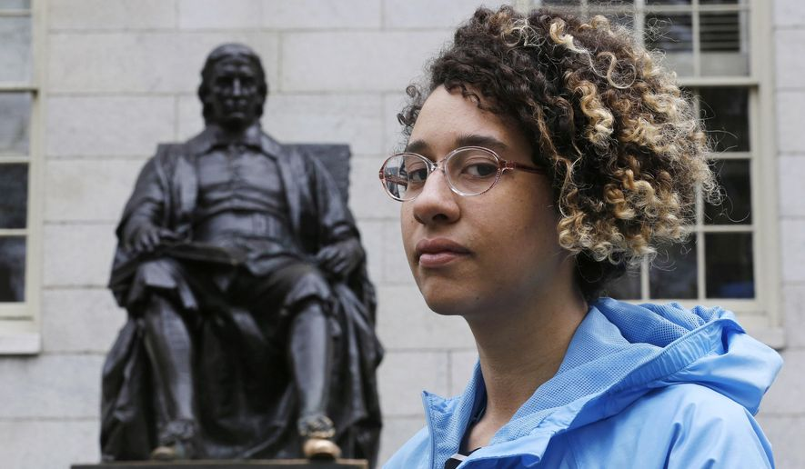 Brianna Suslovic poses at the foot of the John Harvard statue in Harvard Yard prior to presenting a study concerning the history of oppression at Harvard University in Cambridge, Mass., Thursday, May 5, 2016. A group of Harvard students delivered lessons as part of a new research project meant to cast light on the darker corners of the university's past, and to lift up figures that history has long overlooked. (AP Photo/Charles Krupa) **FILE**