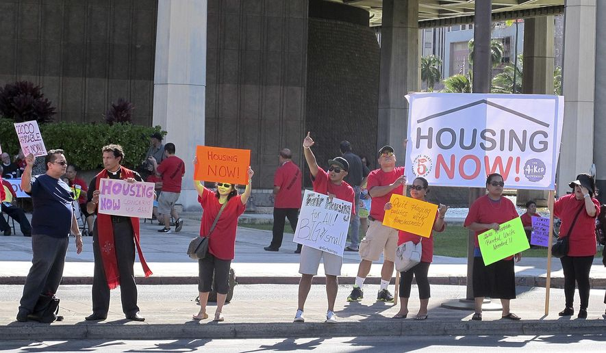 In this April 21, 2016 photo, affordable housing and homeless advocates rally outside the state capitol in Honolulu. Hawaii lawmakers set aside $12 million to tackle the highest rate of homelessness in the nation,  a crisis that has left families with children living on sidewalks alongside the beaches of paradise. (AP Photo/Cathy Bussewitz)