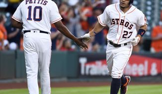 Houston Astros' Jose Altuve (27) shakes hands with third base coach Gary Pettis (10) after hitting a solo home run off of Seattle Mariners starting pitcher Wade Miley in the first inning of a baseball game, Thursday, May 5, 2016, in Houston. (AP Photo/Eric Christian Smith)