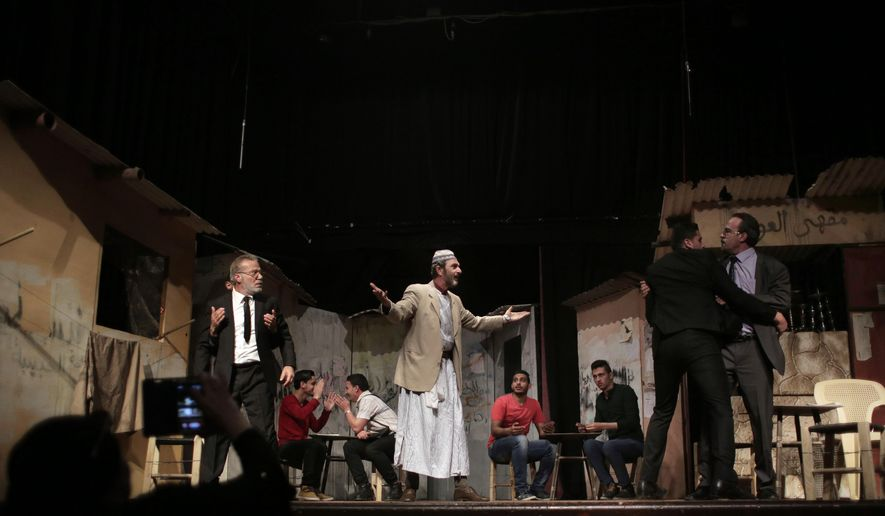 """In this Thursday, April 28, 2016 photo, Palestinian actors perform a Gaza version of Shakespeare's """"Romeo and Juliet"""" play on the stage of a cultural center in Gaza City. Shakespeare's """"Romeo and Juliet"""" has opened to audiences in the Gaza Strip, albeit with a distinctly Palestinian twist. Instead of the forbidden love story of Renaissance-era European aristocracy, the star-crossed young couple in Gaza's version of the play is divided by politics stemming from the deep internal Palestinian split between two rival movements: Gaza's ruling Islamic militant group Hamas and the Fatah party. (AP Photo/Khalil Hamra)"""