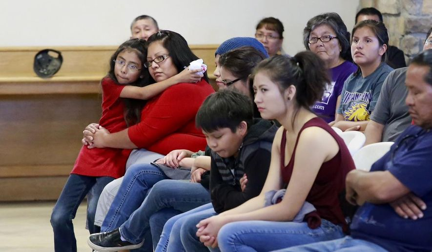 Kynareth Longoria, 7, left, and Letitia Buck, second from left, and other family members mourn for Ashlynne Mike during a vigil for her at the Nenahnezad Chapter House., on Wednesday, May 4, 2016, in Fruitland, N.M. Tom Begaye Jr. was arrested later Tuesday in the death of 11-year-old Ashlynne Mike. He made his first appearance Wednesday before a federal magistrate in Farmington. (Steve Lewis/The Daily Times via AP) MANDATORY CREDIT