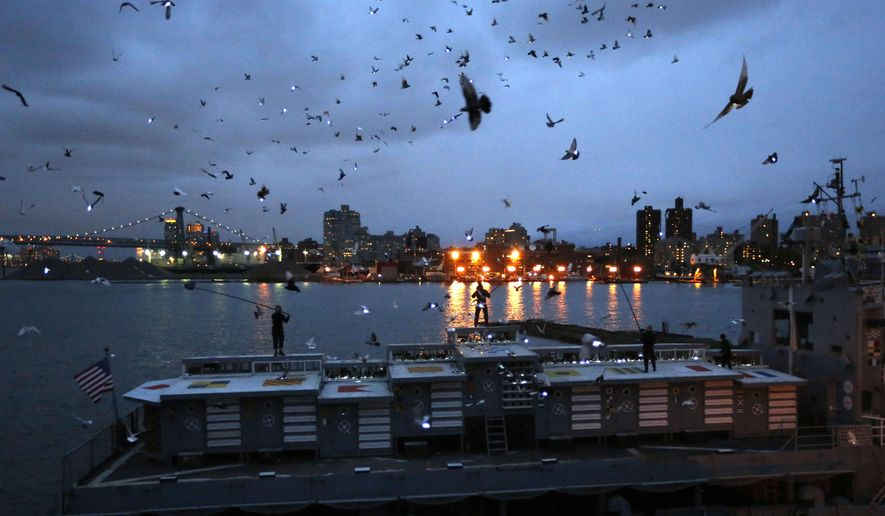 """Pigeons wearing LED lights fly above their coops on board the Baylander, a decommissioned naval ship docked at the Brooklyn Navy Yard, Thursday, May 5, 2016, in New York. The 30-minute performance was part of artist Duke Riley's """"Fly By Night"""" creation. (AP Photo/Kathy Willens)"""
