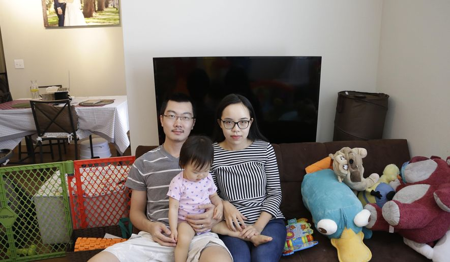 In this Wednesday, May 4, 2016, photo, Wei Wang poses with his wife and daughter in their Houston apartment. The Wangs and several other foreign investors had been banking on their investments in a biomedical research facility in northern Vermont to get green cards. (AP Photo/Pat Sullivan)