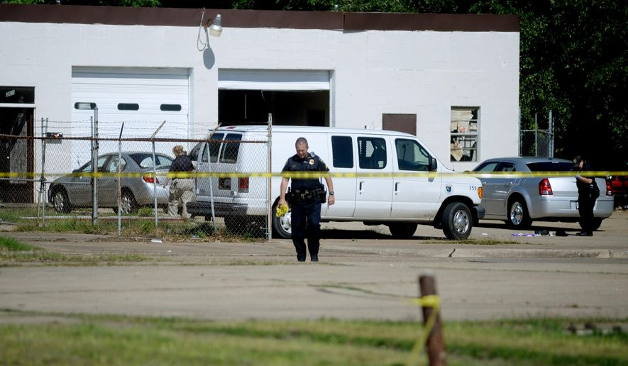 Shreveport police officers gather evidence from a shooting in the 500 block of Seneca, in Shreveport, La., Thursday, May 5, 2016. Masked gunmen burst in on a card game at a north Shreveport tire shop early Thursday and shot several men, Shreveport police said. (Henrietta Wildsmith/The Shreveport Times via AP) MAGS OUT; MANDATORY CREDIT SHREVEPORTTIMES.COM;  NO SALES