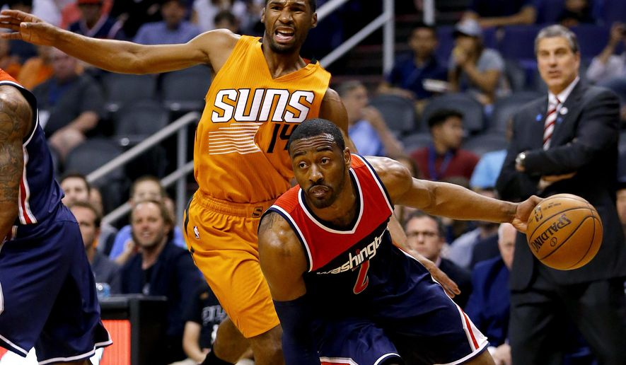 FILE - In this April 1, 2016 file photo, Washington Wizards guard John Wall (2) drives past Phoenix Suns guard Ronnie Price (14) during the first half of an NBA basketball game in Phoenix. The Washington Wizards say All-Star guard Wall underwent left knee surgery and is expected to be ready for the start of next season. (AP Photo/Matt York, File)