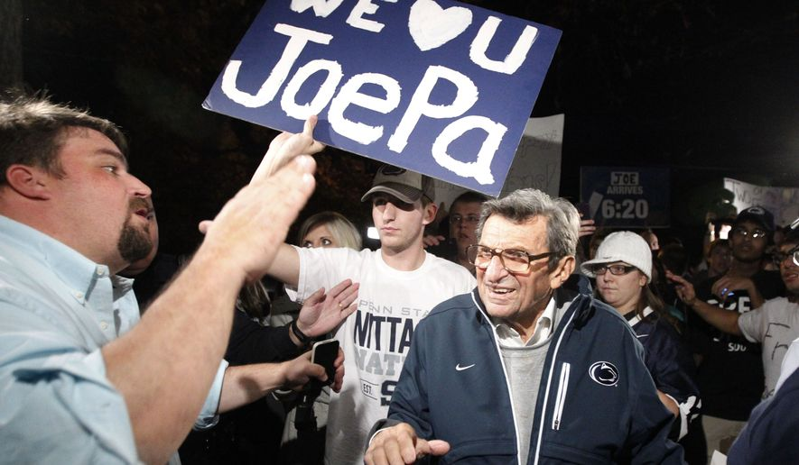 """In this Nov. 8, 2011, file photo, Scott Paterno, left, looks on as students greet his father Penn State football coach Joe Paterno as he arrives at his home in State College, Pa. Scott Paterno said in a tweet sent May 6, 2016, that an allegation made by insurers that a boy told the longtime Penn State football coach in 1976 that he had been molested by former assistant coach Jerry Sandusky is """"bunk."""" (AP Photo/Matt Rourke, File)"""