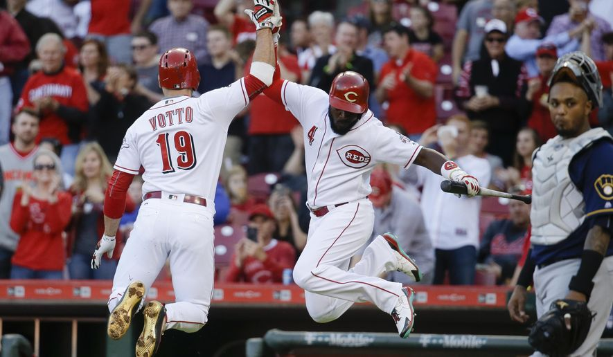 Cincinnati Reds' Joey Votto (19) celebrates with teammate Brandon Phillips (4) after hitting a solo home run off Milwaukee Brewers starting pitcher Tyler Cravy in the first inning of a baseball game, Friday, May 6, 2016, in Cincinnati. (AP Photo/John Minchillo)